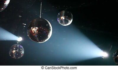 mirror-balls and light lamps in smoke hang on ceiling in...