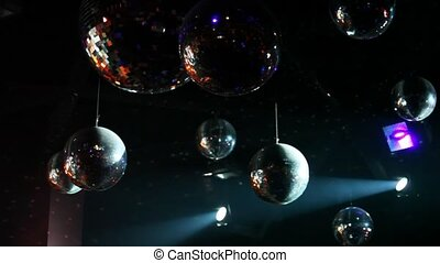 many mirror-balls and light lamps hang on ceiling in night...