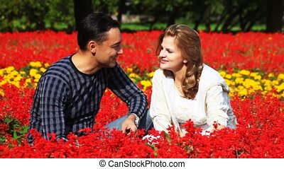 couple sit in park in flowers, smell flowers and smile