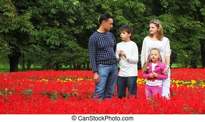 family with boy and girl stay in flowers in park and talk