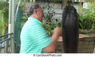 Boxing Workout - Middle aged man works out with a punching...