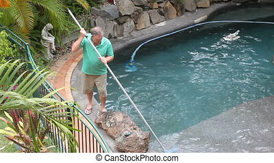 Cleaning Pool Corner - Middle aged man cleans the corner his...