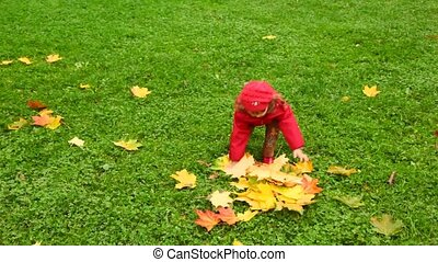 little girl throws up leafs in autumn park