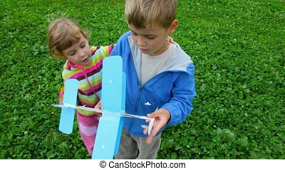 little girl and boy playing with toy aircraft