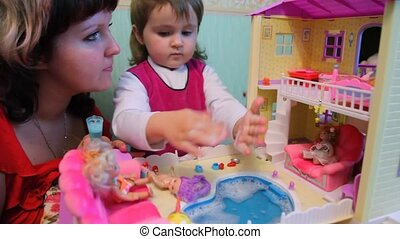 daughter with mother bathes plastic doll