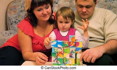 daughter with parents playing cubes