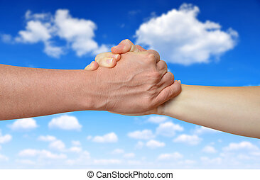 Handshake of friendship on the background blue sky