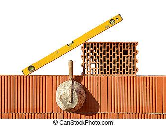 Masonry tools on red brick wall. Bricklaying work.