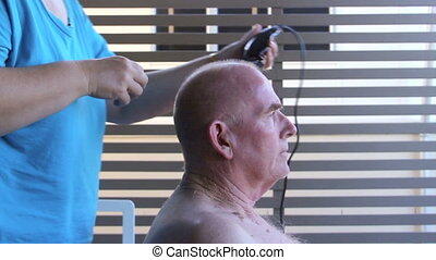Hair Cut - Profile view of a middle aged elderly man getting...