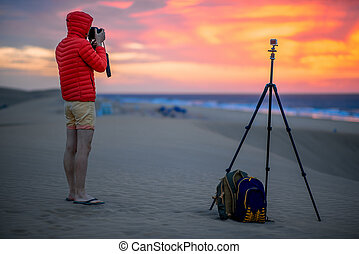 Photographer working outside in the early morning -...