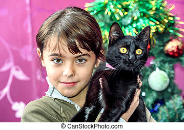 Happy eight year old girl with black cat for Christmas gift