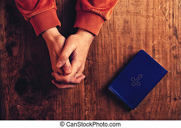 Christian woman praying with hands folded and fingers...