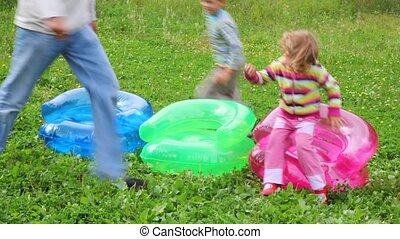 family of three running around inflatable armchairs