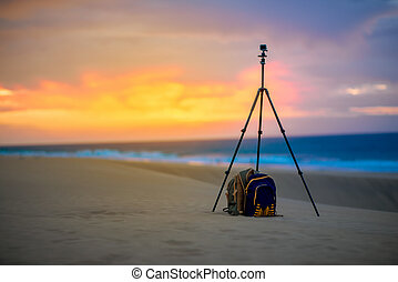 Small video camera on the tripod with backpack outside -...