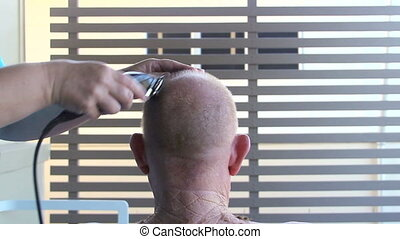 Head Shave - Rear view of a middle aged elderly man getting...