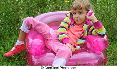 little girl with telephone sitting on inflatable armchair