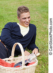 Leisure time - Young blond guy lying on grass with picnic...