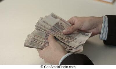 Businessman counts money in hands. People rubles