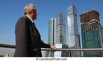 senior man in suit looks at skyscrapers construction