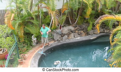 Man Walks Cleaning Pool - Middle aged man walks around with...