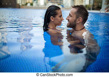 Couple in the pool - Interesting young couple relaxing in...