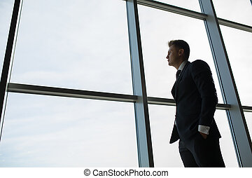 Man at the window - Busy man in a dark suit expensive at a...