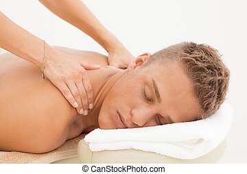 Massage session - Young blond man enoying massage session in...