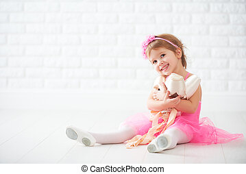 little child girl dreams of becoming ballerina with ballet...