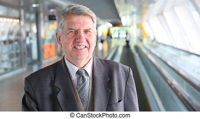 senior man in suit moving down on escalator