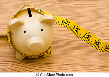 Measuring your success - A piggy bank with a measuring tape,...