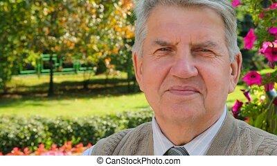 portrait of smile senior man on park background - Portrait...