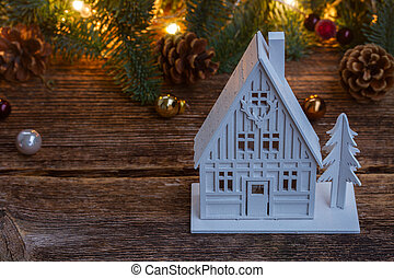 White christmas house with fir tree and defocused lights