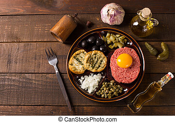 top view of beef tartar - fresh beef tartar with egg, onion,...