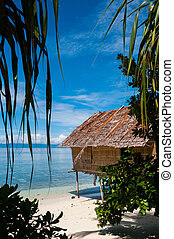 Nipa Hut on stilts at a Beautiful white sand Beach in front of the ocean