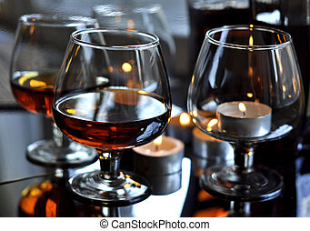 Cognac in a glass - a glass of cognac and candles and...