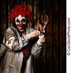 Monster clown checking the pulse on a severed hand - Monster...