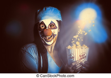 Scary clown watching horror movie in THEATER