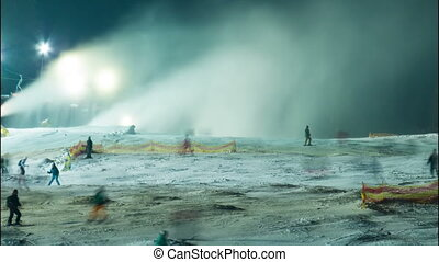 Night skiing at the ski slopes and snow cannons. Timelapse -...