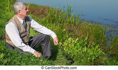 senior man sitting by pond