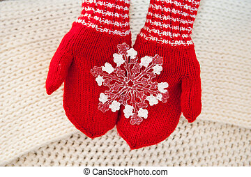woman hand in red gloves holding white big snowflake