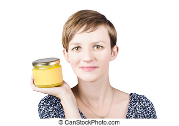 Beautiful young woman displaying jar of ghee - Beautiful...