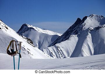 Ski mask on ski poles and off-piste slope in sun day