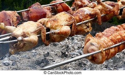 Rows of chickens and pork knuckle cooking on a rotisserie,...