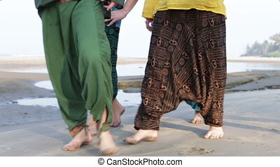 guys in colorful Indian national trousers walk along sand...