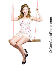 Beautiful fifties pin up girl smiling on swing - Isolated...