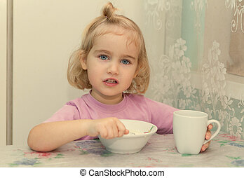 Little girl eats porridge from sitting at the table - Little...