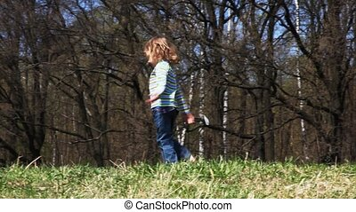 girl turns and goes across field in spring