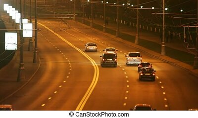 Cars go on highway at night in a city. time lapse