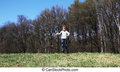 boy jumps and waves hands across field in spring