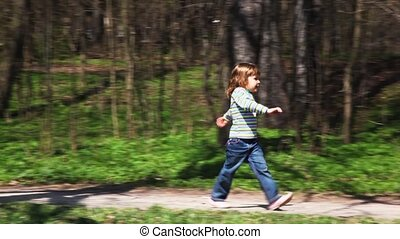 girl goes towards boy on bicycle on forest road in spring